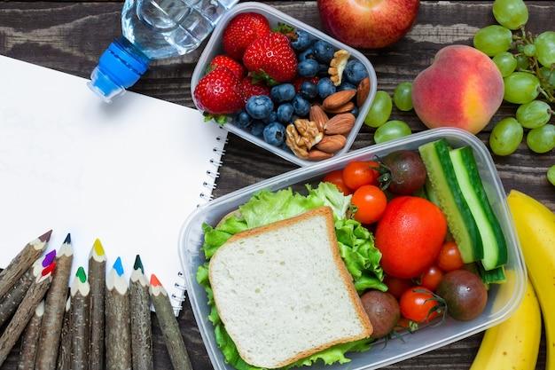 Школьные ланч-боксы с бутербродом, свежими фруктами и овощами