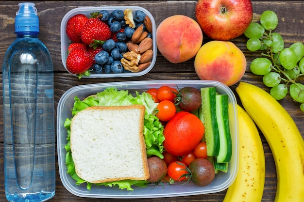 School lunch boxes with sandwich, fresh fruits and vegetables