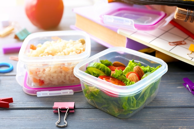 School lunch boxes with tasty food and stationery on wooden