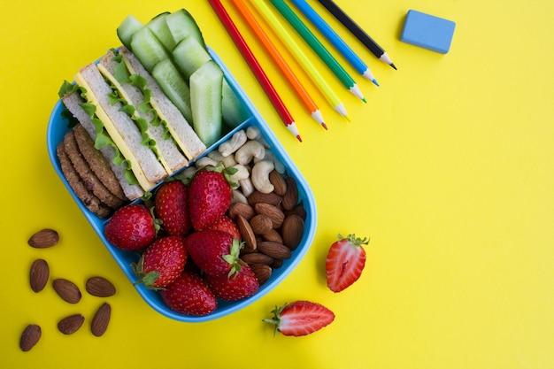 青いボックスの学校給食と黄色の背景の学校の文房具。上面図。スペースをコピーします。
