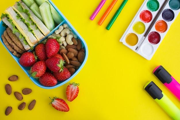 青いボックスと黄色の背景に学校の文房具で学校給食 Premium写真
