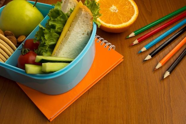 箱の鉛筆とテーブルの上のノートで学校給食