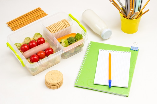 School lunchbox on table with notebook pen, and bottle of yogurt