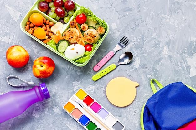 Школьный ланч-бокс со здоровыми закусками и школьными принадлежностями