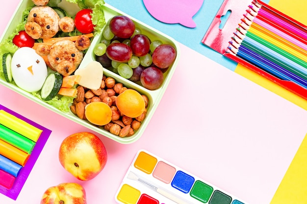 School lunchbox with healthy snack and school supplies