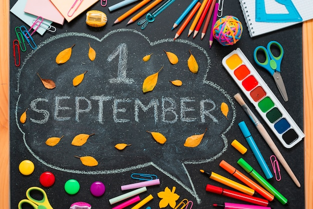 Forniture scolastiche colorate, matite e una nuvola disegnata con spazio di copia per il testo.
