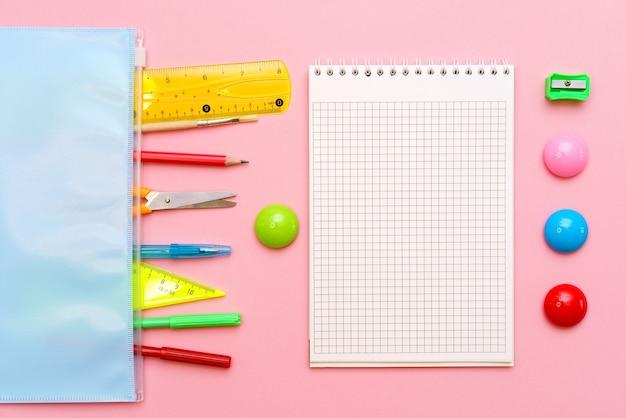 Школьная тетрадь и различные офисные принадлежности обратно в школу на ярко-розовом фоне
