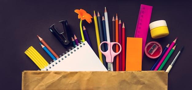 学校のノートと茶色の背景に紙袋の様々な文房具。学校のコンセプトに戻ります。学校や事務用品のフレーム。