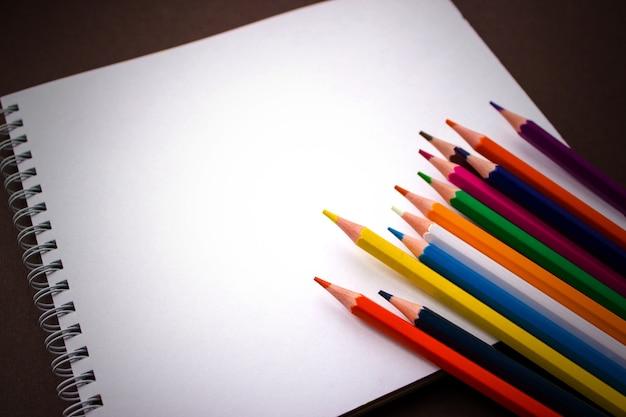 学校のノート、茶色の背景にアートスケッチパッド色鉛筆。