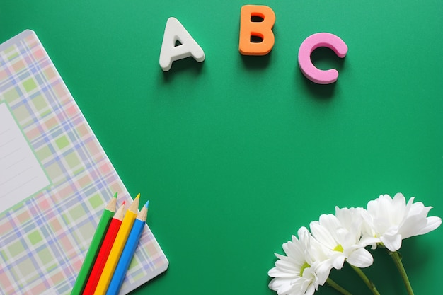 School notebook and colored pencils next to the letters abc and white chrysanthemums on a green background.