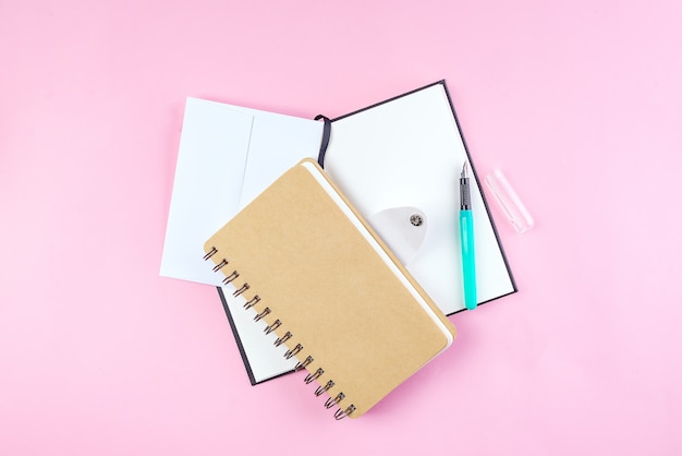 School notebook on a pink background, spiral notepad on a table