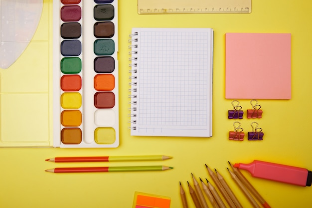 School notebook and stationery over yellow table. back to school abstract background