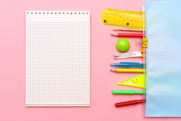 School notebook and various office supplies back to school concept on bright pink background