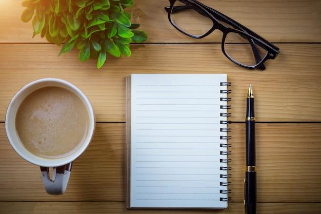 空のページと木製のテーブルにコーヒーのカップの隣に眼鏡を持つ学校のノートブック
