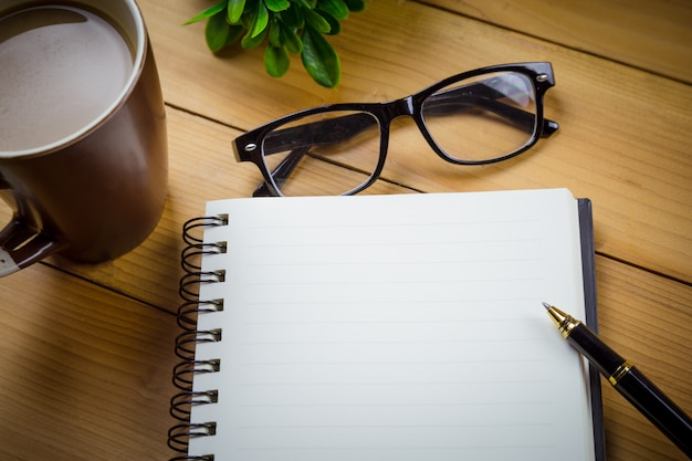 School notebook with blank pages and with glasses next to cup of coffee on wooden table