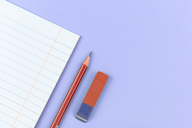 紫色のオフィステーブルに鉛筆と消しゴムの学校構成の背景を持つ学校のノート