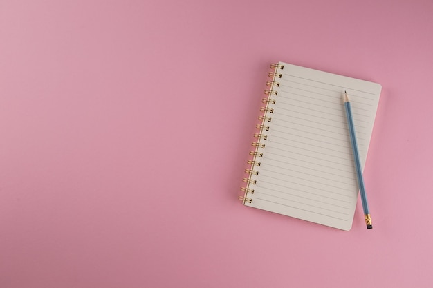 School notebook with pencil on a pink background.