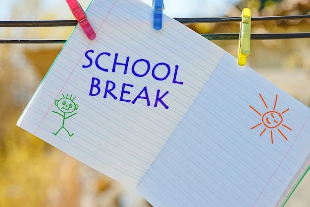 洗濯ばさみにぶら下がっているschoolbreakの碑文が書かれた学校のノート