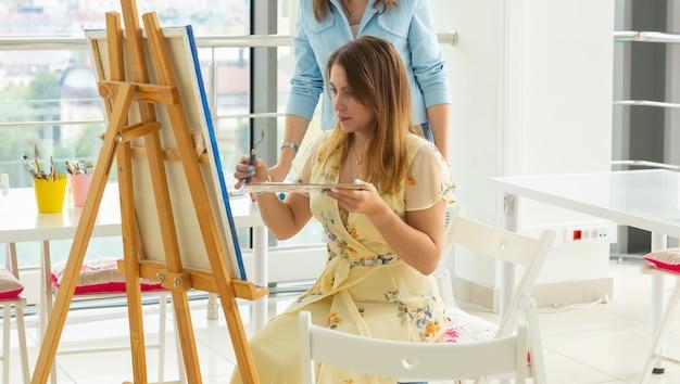 芸術学校、芸術大学、若い学生のグループのための教育。幸せな若い女性の笑顔、先生と一緒に絵を描くことを学ぶ女の子。