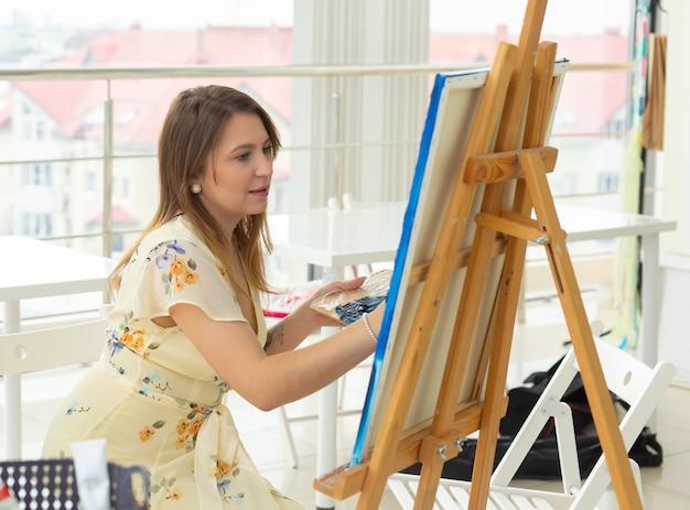 芸術学校、芸術大学、若い学生のグループのための教育。幸せな若い女性の笑顔、女の子がペイントを学ぶ。