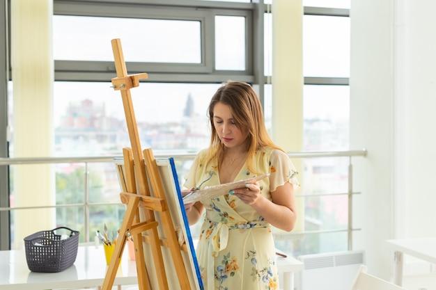 芸術学校、芸術大学、若い学生のグループのための教育。幸せな若い女性の笑顔