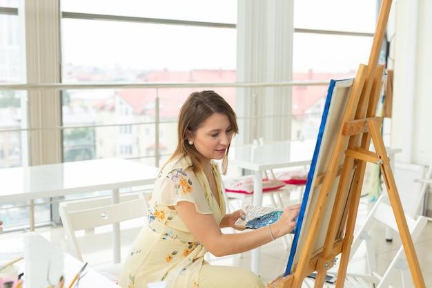 예술 학교, 예술 대학, 어린 학생들을위한 교육. 웃 고 행복 한 젊은 여자
