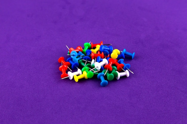 School office colored pins buttons isolated on purple