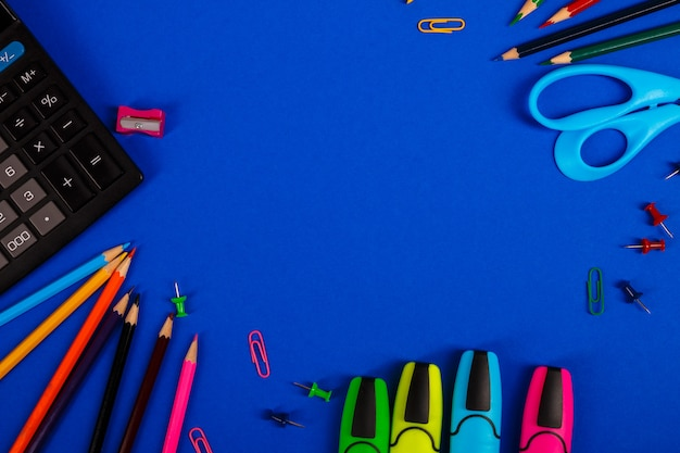 School or office stationery on blue background. back to school. frame, copy space. supplies