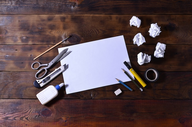 A school or office still life with a white blank sheet of paper and many office supplies.
