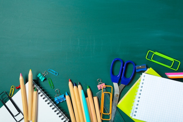 School and office supplies on blackboard background