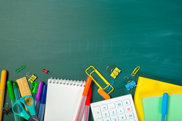 School and office supplies on blackboard