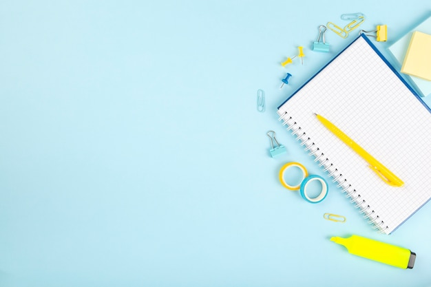 School office supplies on blue background. back to school concept. top view. copy space