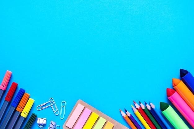 学校の事務用品は、水色の背景に下から横たわっていますカラフルな鉛筆フェルトチップペンブラシ