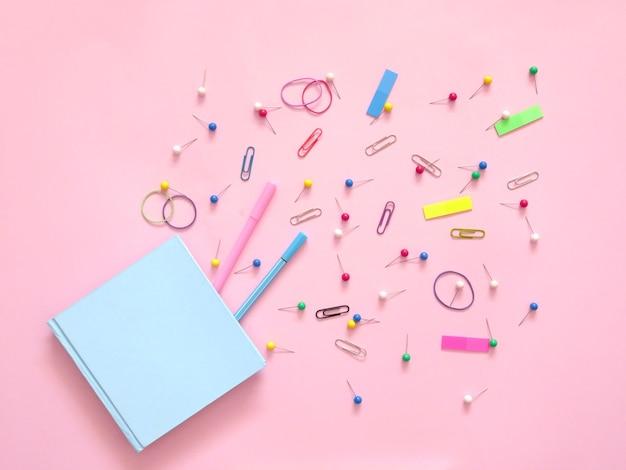 ピンクの背景に学校の事務用品。学校のコンセプトに戻る。