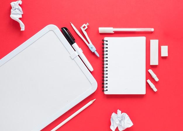School and office supplies on red background