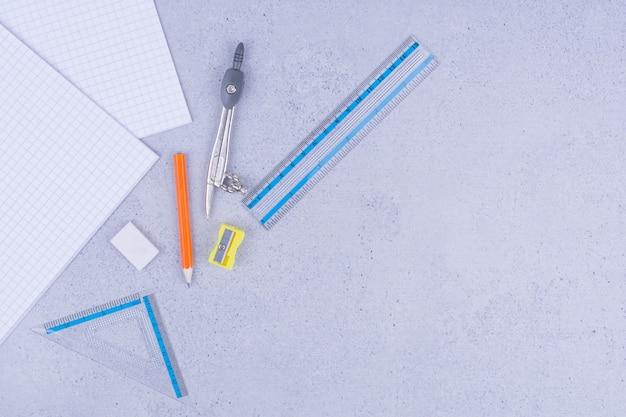Strumenti di scuola o ufficio con note adesive su grigio.