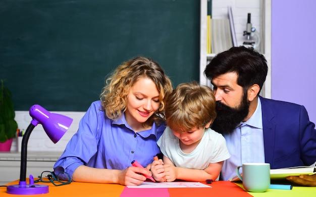 一年生の幸せな家族の学校の学校の男の子はかわいい生徒と彼の父と一緒に数学を学校に通し、