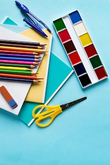 School set of accessories from notebooks, compasses, pencils, scissors, paints and an eraser on a blue background,