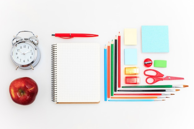 School set with notebooks, pencils, brush, scissors and apple on white
