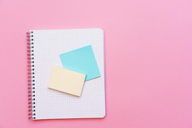ピンクの背景のステッカーの学校のスパイラルノートは、メモ用のシートステーショナリーの上にあります...