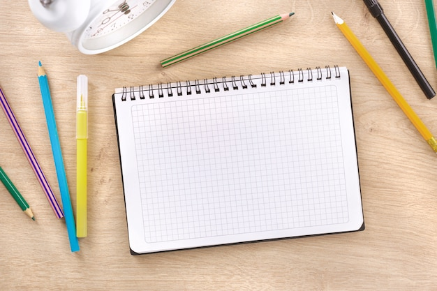 School spiral notebook with markers on wooden background top view