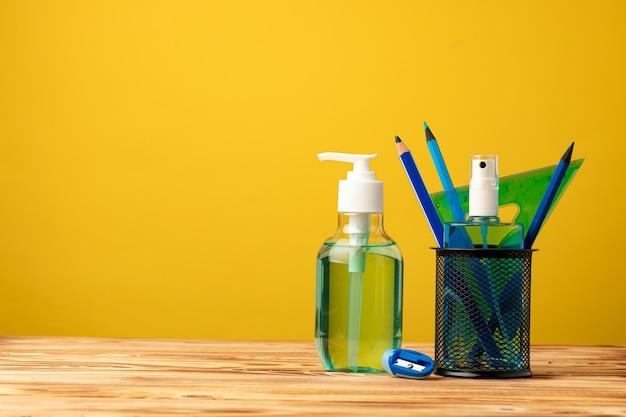 학교 문구 및 손 소독제. 코로나 바이러스 전염병 동안 학교 개념으로 돌아 가기