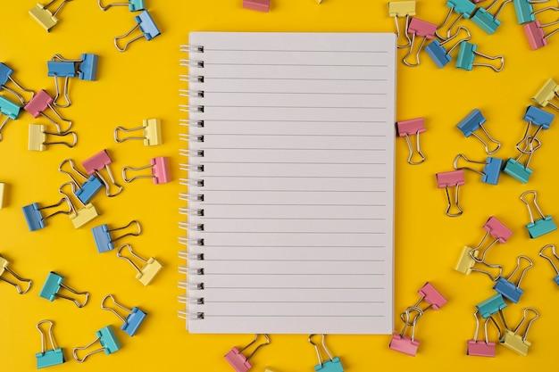 学校の文房具とペーパークリップの上面図のコピースペースと黄色の背景に紙のノート