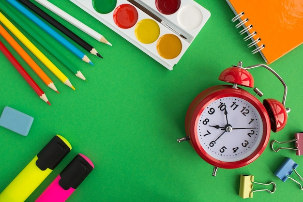 学校の文房具と赤い目覚まし時計。上面図。スペースをコピーします。