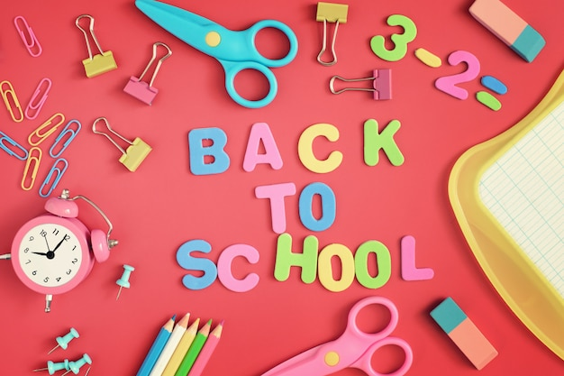 School and stationery are scattered on the red background. in the center of the inscription in colored letters, back to school.