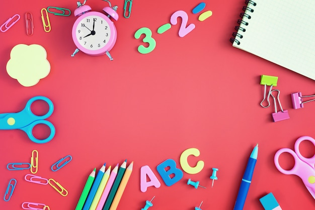 School and stationery are scattered on the red background. in the center there is an empty space for an inscription or text.