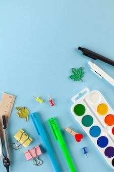 School stationery on a blue background. concept of stationery store, preparation for school, knowledge day.