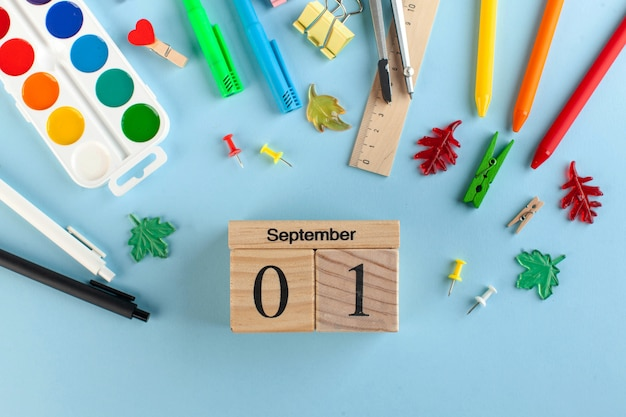 School stationery on a blue background. wooden calendar september 1. knowledge day concept.