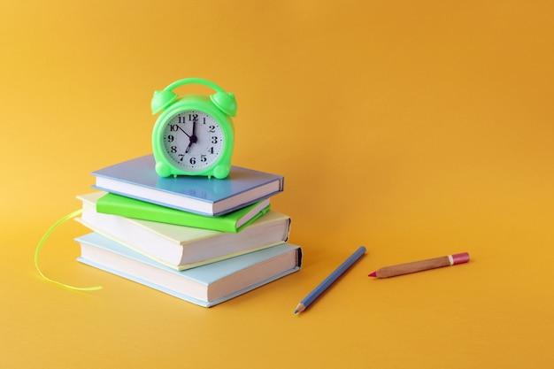 School stationery, books, alarm clock on bright background