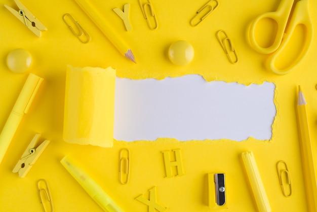 학교 편지지 개념입니다. 위쪽 오버헤드 뷰 클로즈업 사진 위에 노란색 편지지와 찢어진 밝은 노란색 종이 카피스페이스가 있는 흰색 배경